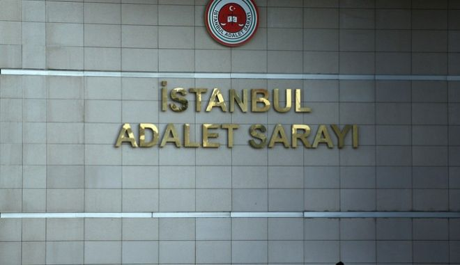 A police officer guards a court in Istanbul, Wednesday, Jan. 31, 2018, with the sign reading in Turkish: 'Justice Palace'.  Turkey's state-run news agency Anadolu Agency says Wednesday the court has sentenced three people to life prison terms for their involvement in an Islamic State group suicide bomb attack in Jan. 2016 at Istanbul's historic Sultanahmet district that killed 12 German tourists and wounded 15 people, including nine Germans and citizens of Norway, Peru and South Korea. (AP Photo/Lefteris Pitarakis)