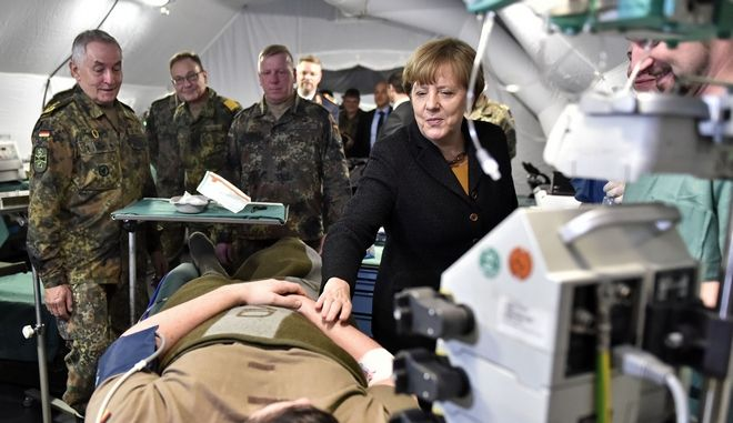 German chancellor Angela Merkel, right, touches a soldier playing an injured at a presentation of a mobile hospital during a visit of the German Army medical service in Leer, northern Germany, Monday, Dec. 7, 2015. Germany's parliament voted last week to send military support in the fight against Islamic State militants in Syria. (AP Photo/Martin Meissner)