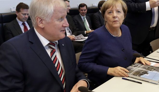 The German Chancellor and Chairwomen of the German Christian Democratic Party (CDU), Angela Merkel, right, and the chairman of the German Christian Social Union Party (CSU), Horst Seehofer, left,arrive for the parliamentary caucus of Merkel's conservative Union bloc in Berlin, Germany, Tuesday, Sept. 26, 2017. (AP Photo/Michael Sohn)