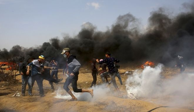 Παλαιστίνιοι διαδηλωτές τρέχουν για να καλυφθούν απ' τα δακρυγόνα, σε νέες βίαιες συγκρούσεις που ξέσπασαν στη Λωρίδα της Γάζας