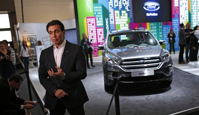 In a Monday, Feb. 22, 2016 file photo, Ford CEO Mark Fields talks during an interview next to the new Kuga SUV car, during the Mobile World Congress Wireless show,in Barcelona, Spain. Ford Motor Co. is going ahead with plans to move small-car production from the U.S. to Mexico despite President-elect Donald Trump's recent threats to impose tariffs on companies that move work abroad. Fields said Ford's plan to move production of the Ford Focus from Michigan to Mexico will proceed, in part because U.S. consumers demand low prices for small cars. (AP Photo/Francisco Seco, File)