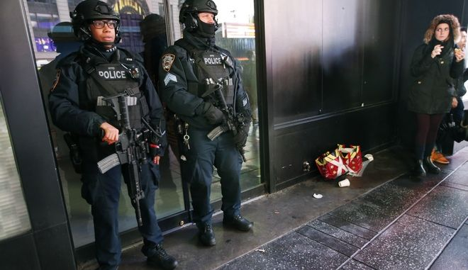 Heavily armed counterterrorism officers take shelter from the rain beneath an overhang in Times Square, Thursday, Dec. 29, 2016, in New York, as the New York Police department began ramping up security for the city's massive New Year's Eve celebration. The department says they are up to the task of deterring the type of deadly truck attacks that occured this year in Nice and more recently in Berlin. (AP Photo/Kathy Willens)