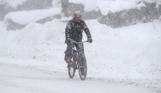 A man rides on his bicycle as fresh snow falls, Friday, Dec. 29, 2017, in Erie, Pa. The cold weather pattern was expected to continue through the holiday weekend and likely longer, according to the National Weather Service, prolonging a stretch of brutal weather blamed for several deaths, crashes and fires. (AP Photo/Tony Dejak)