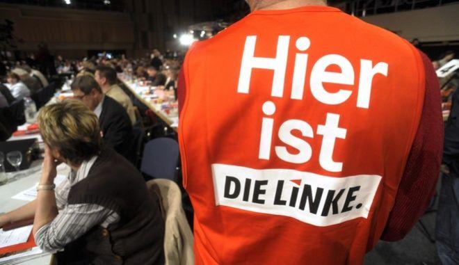 """Ein Mitglied der Wahlkommision steht am Sonntag, 16. Mai 2010, mit einer Aufschrift """"Hier ist die Linke"""" auf der Weste auf dem Bundesparteitag der Partei """"Die Linke"""" in Rostock. (apn Photo/Thomas Haentzschel) ----- A party member wears a vest with the slogan """"Here is left"""" at a federal party convent of the  left party """"Die Linke"""" in Rostock, northern Germany, Sunday, May 16, 2010. (apn Photo/Thomas Haentzschel)"""