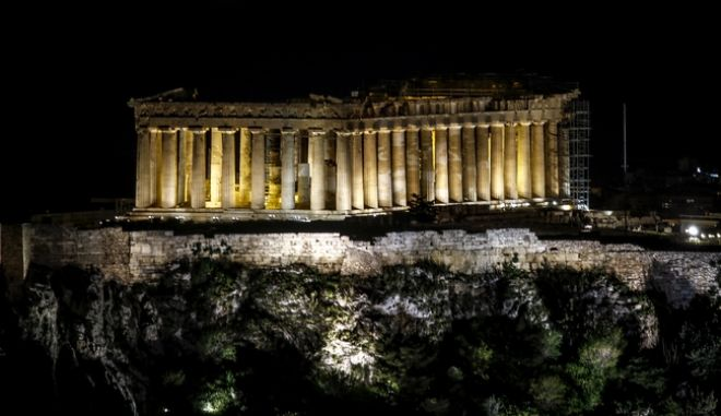 """Ο βράχος της Ακρόπολης φωταγωγημένος λίγα λεπτά πριν σβήσουν οι προβολείς προκειμένου να συμμετέχει η πόλη της Αθήνας στην """"Ώρα της Γης"""", στην παγκόσμια προσπάθεια ευαισθητοποίησης για την αντιμετώπιση της κλιματικής αλλαγής. το Σάββατο 24 Μαρτίου 2018"""
