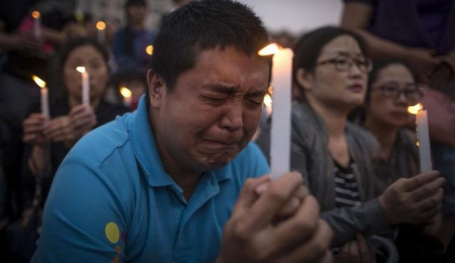 A man reacts during a candle light vigil by locals and family members of passengers onboard the capsized cruise ship in Jianli county  in southern China's Hubei province Thursday June 4, 2015.  Rescuers cut three holes into the overturned hull of a river cruise ship in unsuccessful attempts to find more survivors Thursday.  (Chinatopix Via AP) CHINA OUT