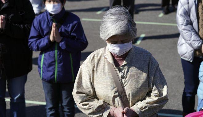 Ιάπωνες πολίτες με μάσκες προσεύχονται