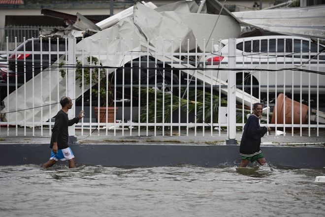 People walk through a flooded area after the impact of Hurricane Maria, which hit the eastern region of the island, in Humacao, Puerto Rico, Wednesday, September 20, 2017. The strongest hurricane to hit Puerto Rico in more than 80 years destroyed hundreds of homes, knocked out power across the entire island and turned some streets into raging rivers in an onslaught that could plunge the U.S. territory deeper into financial crisis. (AP Photo/Carlos Giusti)