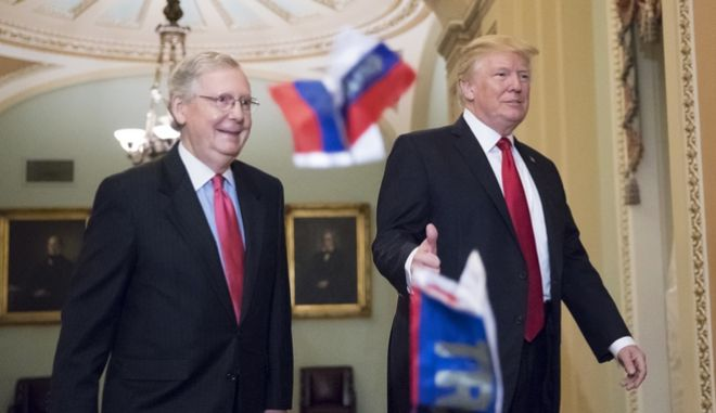 """Small Russian flags bearing the word """"Trump"""" are thrown by a protester toward President Donald Trump, as he walks with Senate Majority Leader Mitch McConnell, R-Ky., on Capitol Hill to have lunch with Senate Republicans and push for his tax reform agenda, in Washington, Tuesday, Oct. 24, 2017. (AP Photo/J. Scott Applewhite)"""