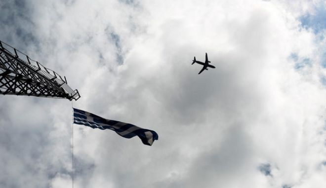 An airoplane flies over a waving Greek national flag, in Thessaloniki, Greece on April 6, 2015.