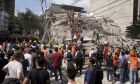 Volunteers and first responders look for survivors in a collapsed building after an earthquake struck Mexico City, Tuesday, Sept. 19, 2017. The 7.1 earthquake stunned central Mexico, killing more than 100 people. (AP Photo/Pablo Ramos)