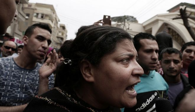 A woman talks to a journalist outside the St. George's Church after a deadly suicide bombing, in the Nile Delta town of Tanta, Egypt, Sunday, April 9, 2017. Bombs exploded at two Coptic churches in the northern Egyptian cities of Tanta and Alexandria as worshippers were celebrating Palm Sunday, killing over 40 people and wounding scores more in assaults claimed by the Islamic State group. (AP Photo/Nariman El-Mofty)