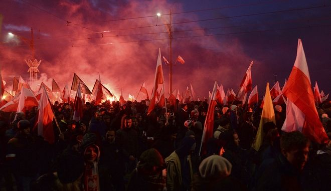 Demonstrators burn flares and wave Polish flags during the annual march to commemorate Poland's National Independence Day in Warsaw, Poland, Saturday, Nov. 11, 2017. Thousands of nationalists marched in Warsaw on Polands Independence Day holiday, taking part in an event that was organized by far-right groups. (AP Photo/Czarek Sokolowski)