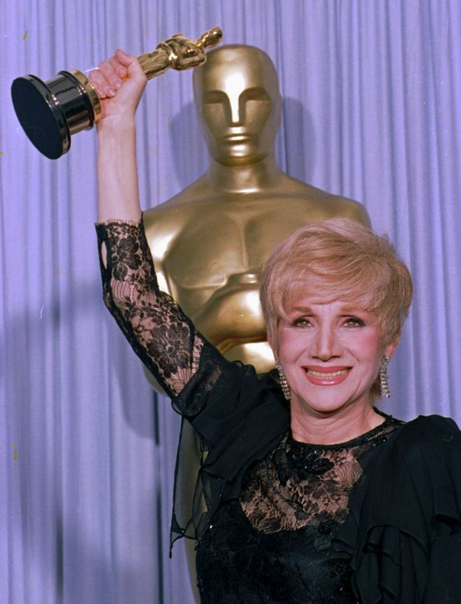 Olympia Dukakis holds her Oscar high April 11, 1988, as she stands backstage at the Shrine Auditorium in Los Angles after being honored at the 60th Academy Awards as best supporting actress for her role in