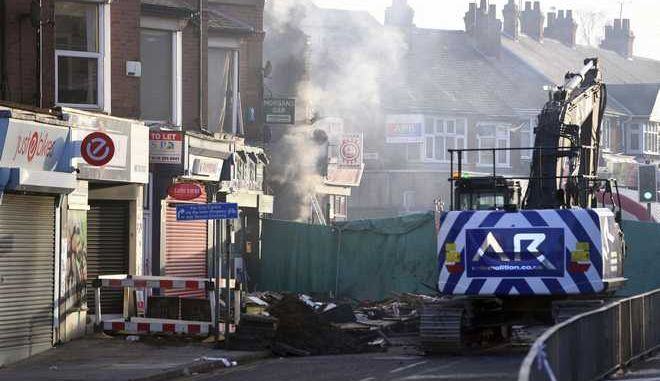 Emergency personnel continue to work at the scene of an explosion and fire Sunday night which destroyed a shop and building above in Leicester, England,  Monday Feb. 26, 2018, where four people were killed and others seriously injured.  Emergency service officials say Monday four people have been hositalised but more people may be missing and a search and rescue operation is continuing. (Joe Giddens/PA via AP)