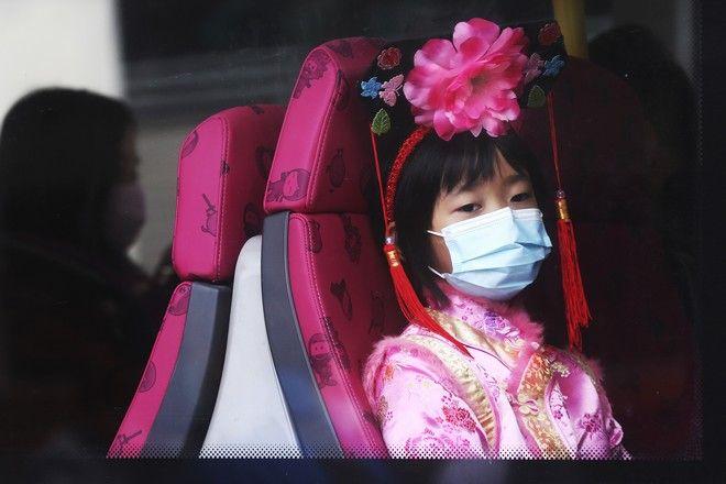 Κορίτσι σε λεωφορείο φοράει μάσκα για να προστατευτεί από τον νέο κοροναϊό