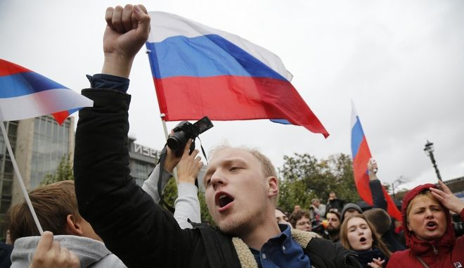 Demonstrators hold Russian flags during a rally in Moscow, Russia, Saturday, Oct. 7, 2017. Opposition leader Alexei Navalny has worked to organize protests in support of his presidential bid across Russia on Saturday, President Vladimir Putin's birthday. (AP Photo/Alexander Zemlianichenko)