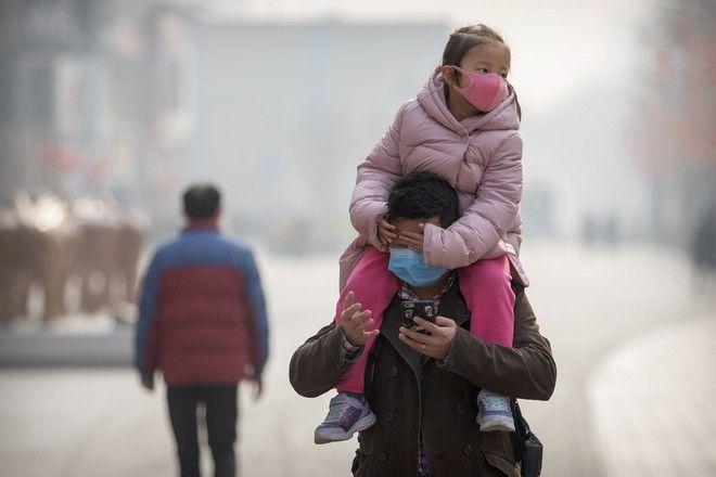Πατέρας και κόρη κάνουν βόλτα φορώντας μάσκα για προστασία από τον νέο κοροναϊό