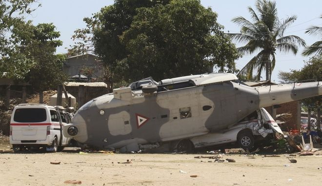 A downed helicopter lays in its side in Santiago Jimitepec, Oaxaca state, Mexico, Saturday, Feb. 17, 2018. The military helicopter carrying officials assessing damage from the Friday's earth quake crashed killing 13 people and injuring 15, all of them on the ground. (AP Photo/Luis Alberto Cruz Hernandez)