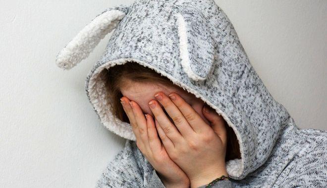 Φοβισμένο κορίτσι κρύβει το πρόσωπό του