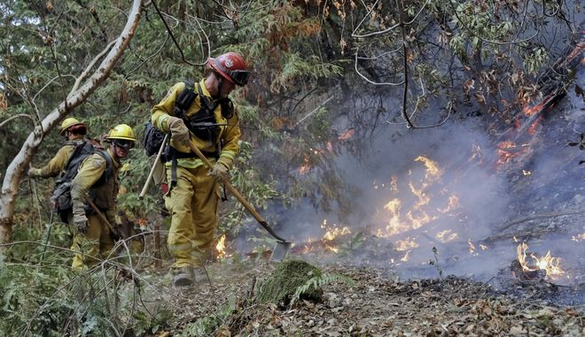 Fire crews build a containment line as they battle a wildfire Tuesday, Oct. 17, 2017, near Boulder Creek, Calif. (AP Photo/Marcio Jose Sanchez)