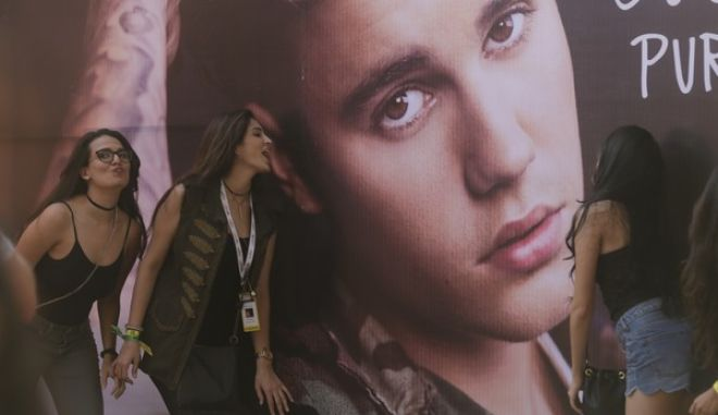 Fans of Canadian singer Justin Bieber pose for photographs in front his poster ahead of a concert by him in Mumbai, India, Wednesday, May 10, 2017. (AP Photo/Rafiq Maqbool)