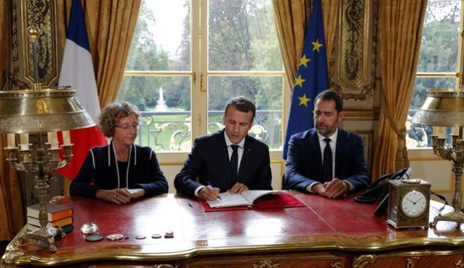 French President Emmanuel Macron, center, signs documents in front of the media to promulgate a new labor bill in his office at the Elysee Palace in Paris, France, as Minister of Labor Muriel Penicaud, left, and Government Spokesman Christophe Castaner look on, Friday, Sept. 22, 2017. Macron has signed Friday five decrees paving the way to the implementation of labor measures aimed at boosting growth, his first major reform since his election. (Philippe Wojazer/Pool Photo via AP)