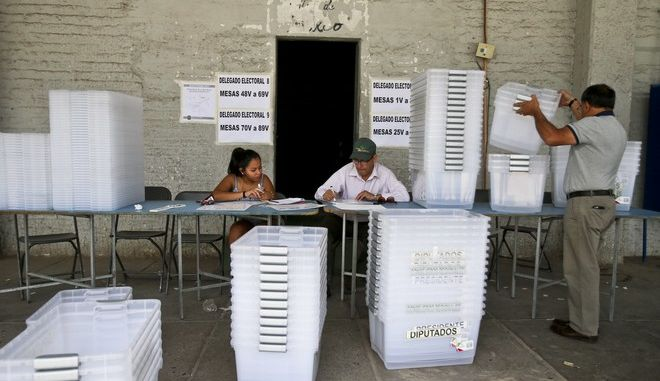 Poll workers are prepares for the presidential runoff, in a national stadium used as a polling station center in Santiago, Chile, Saturday, Dec. 16, 2017.  Turnout is expected to be low on Sunday since voting was made voluntary rather than mandatory in 2012.   (AP Photo/Esteban Felix)