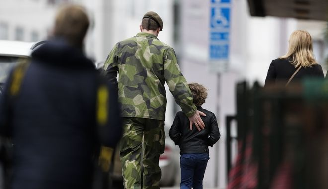 """A soldier and a boy walk away after they offered flowers near the department store Ahlens following a suspected terror attack in central Stockholm, Sweden, Saturday, April 8, 2017. A Swedish prosecutor says a person has been formally identified as a suspect """"of terrorist offenses by murder"""" by driving a hijacked truck into a crowd of pedestrians. (AP Photo/Markus Schreiber)"""