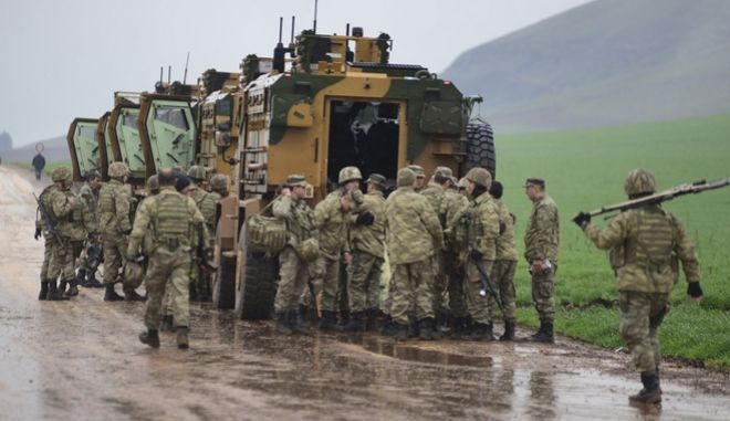 Turkish Army soldiers form a convoy of armoured personnel carriers near the border with Syria, in the outskirts of Hassa, Turkey, Tuesday, Jan. 23, 2018. Turkey's Foreign Minister Mevlut Cavusoglu has announced that a second Turkish soldier has been killed in action in Turkey's military offensive on a Kurdish-held enclave in northern Syria. (Caglar Ozturk/DHA-Depo Photos via AP)