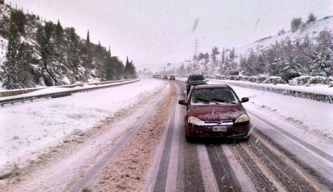 Αυτοκίνητα κινούνται σε δρόμο με χιόνια.