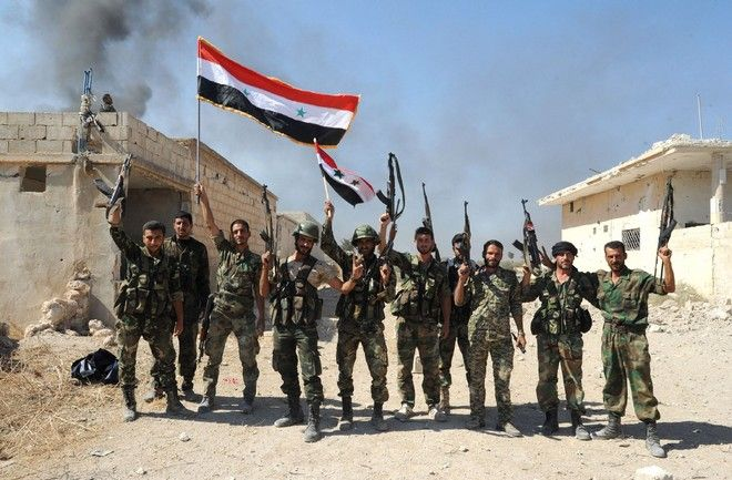 A handout picture released by the official Syrian Arab News Agency (SANA), shows Syrian army units and pro-government forces deploying at an undisclosed location in the Atshan village in central province of Hama,  on October 11, 2015. Regime forces advanced in the central Syrian province of Hama against armed opposition groups in a ground operation backed by Russian air strikes. AFP PHOTO / HO / SANA  === RESTRICTED TO EDITORIAL USE - MANDATORY CREDIT