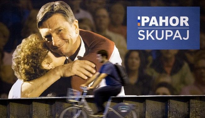 A cyclist rides past a campaign poster of Slovenia's president incumbent Borut Pahor, in Ljubljana, Slovenia, Thursday, Oct. 19, 2017. Slovenia, the Alpine home country of Melania Trump, is holding a presidential election Sunday that incumbent President Borut Pahor _ a former fashion model, like the U.S. first lady _ is favored to win. Eight other candidates are vying for the largely ceremonial, but still influential head of state post.  (AP Photo/Darko Bandic)
