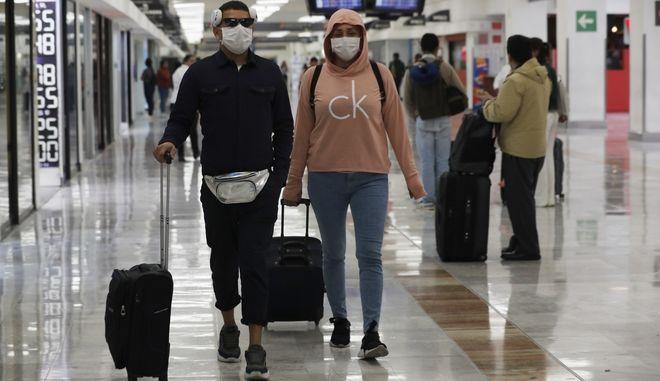 Ταξιδιώτες με μάσκες σε αεροδρόμια.