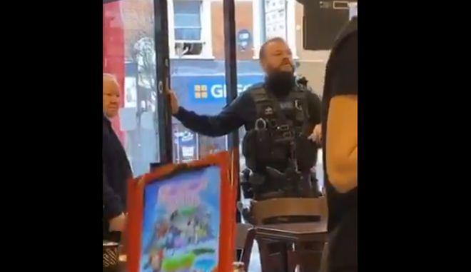 Η στιγμή που ο αστυνομικός ενημερώνει τους θαμώνες του καταστήματος για την τρομοκρατική επίθεση
