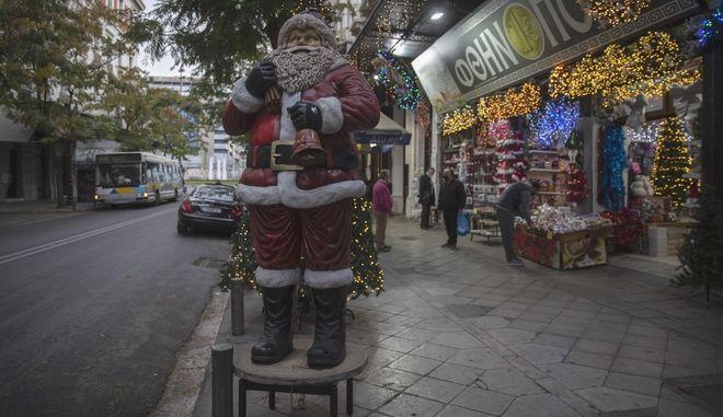 Άγιος Βασίλης έξω από κατάστημα εποχικών ειδών, στα πιο δύσκολα Χριστούγεννα των τελευταίων δεκαετιών.