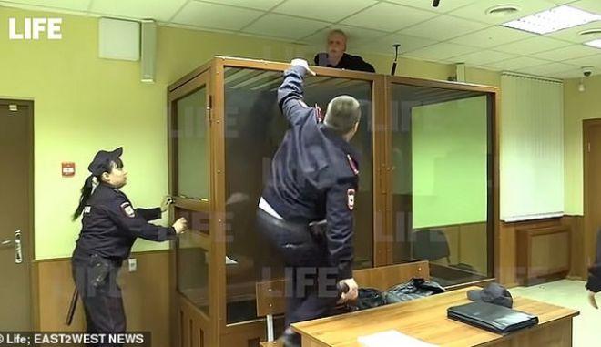 Η στιγμή που ο 18χρονος επιχειρεί να διαφύγει από το ταβάνι της δικαστικής αίθουσας.