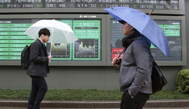 Άνθρωποι περπατούν μπροστά από ηλεκτρονικό πίνακα χρηματιστηρίου στο Τόκιο