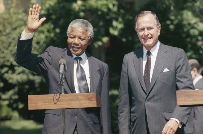 President Bush greets South African leader Nelson Mandela on the South Lawn of the White House in Washington on June 26, 1990. Mandela told Bush that support South Africa has received from the United States - particularly economic sanctions - have been crucial to promoting changes in his country. (AP Photo/Doug Mills)