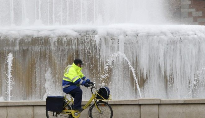 A postman cycles past a partially frozen fountain in front of the Milan medieval Sforza castle, Italy, Tuesday, Feb. 7, 2012 as a cold front continues to affect the country. (AP Photo/Antonio Calanni)