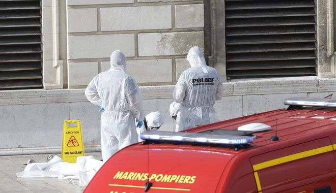 Investigative police officers work at a body outside Marseille 's main train station Sunday, Oct. 1, 2017 in Marseille, southern France. A man with a knife attacked people at the main train station in the southeastern French city of Marseille on Sunday, killing two women before soldiers fatally shot the assailant, officials said. (AP Photo/Claude Paris)