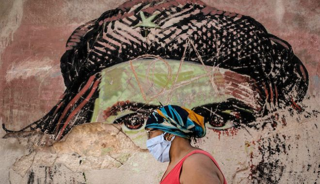 Μια γυναίκα με μάσκα περνάει από τοιχογραφία του Ερνέστο Τσε Γκεβάρα, στην Παλιά Αβάνα της Κούβας, 19 Ιανουαρίου 2021.