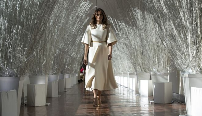 """First lady Melania Trump walks along the East Colonnade decorated in white branches that are part of 2017 holiday decorations with the theme """"Time-Honored Traditions"""" at the White House in Washington, Monday, Nov. 27, 2017. The First Lady honored 200 years of holiday traditions at the White House. (AP Photo/Carolyn Kaster)"""