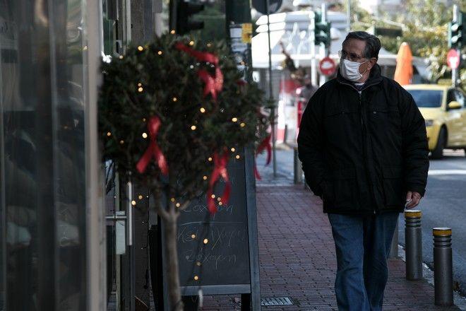 Άντρας με μάσκα περπατά στη Χριστουγεννιάτικη Αθήνα