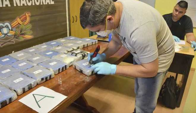 In this Dec. 14, 2016, photo and released on Feb. 22, 2018, by the Argentine Security Ministry, a police officer opens up a package of cocaine found in an annex building Russian embassy in Buenos Aires, Argentina. A Russian diplomatic official and an Argentine police officer are among those arrested after authorities seized a cocaine shipment of 860 pounds (389 kilograms) at the Russian embassy in Buenos Aires that prompted them to launch a yearlong joint investigation to dismantle a drug ring, the government said. (Argentine Security Minister via AP)