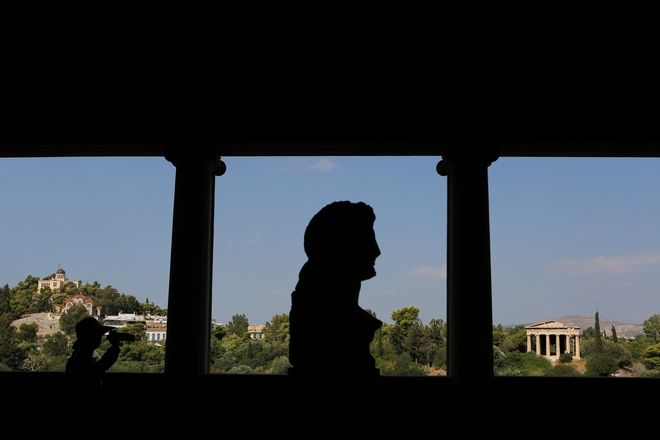 Silhouettes of a tourist , left, and a 2nd century AD bust of Alexander the Great or Eubouleus, a minor Greek deity, are seen from the first floor of the Museum of the ancient Agora, Stoa of Attalos, against the background of the 2,400-year-old temple of Ifestos, in Athens on Friday Aug. 23, 2013. Spending by tourists in Greece surged this summer, central bank data showed earlier this week, confirming forecasts that a record summer season could give the debt-laden country a welcome injection of foreign cash.(AP Photo/Petros Giannakouris)
