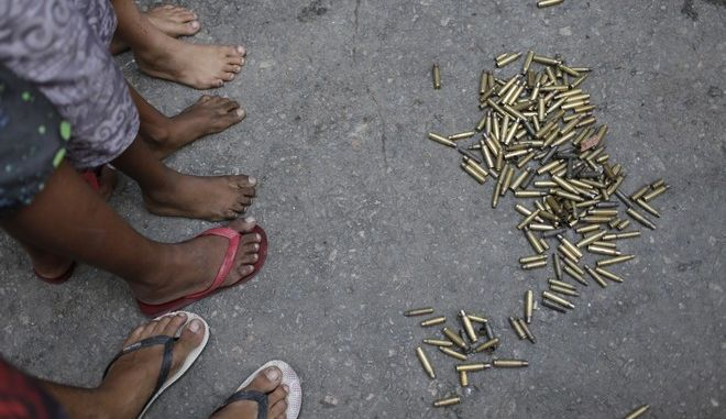 Children stand next to spent bullet casings after a police operation at the Mangueira favela in Rio de Janeiro, Brazil, Friday, June 30, 2017. A 76-year-old woman and her daughter, who tried to come to her aid, have been killed in a shootout between police and drug traffickers in the Rio de Janeiro slum. (AP Photo/Silvia Izquierdo)