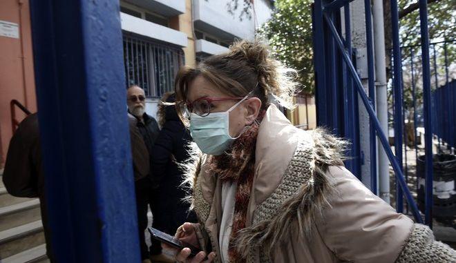 Γυναίκα με μάσκα εισέρχεται σε σχολείο.
