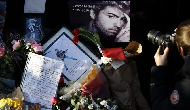 A photographer takes pictures of memorabilia, placed by fans, outside the home of British musician George Michael in London, Tuesday, Dec. 27, 2016. George Michael, who rocketed to stardom with WHAM! and went on to enjoy a long and celebrated solo career lined with controversies, has died, his publicist said Sunday. He was 53.(AP Photo/Frank Augstein)