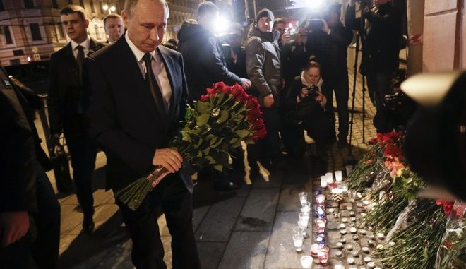 Russian President Vladimir Putin, left, lays flowers at a place near the Tekhnologichesky Institut subway station in St.Petersburg, Russia, Monday, April 3, 2017. A bomb blast tore through a subway train deep under Russia's second-largest city Monday, killing several people and wounding many more in a chaotic scene that left victims sprawled on a smoky platform. (AP Photo/Dmitri Lovetsky)